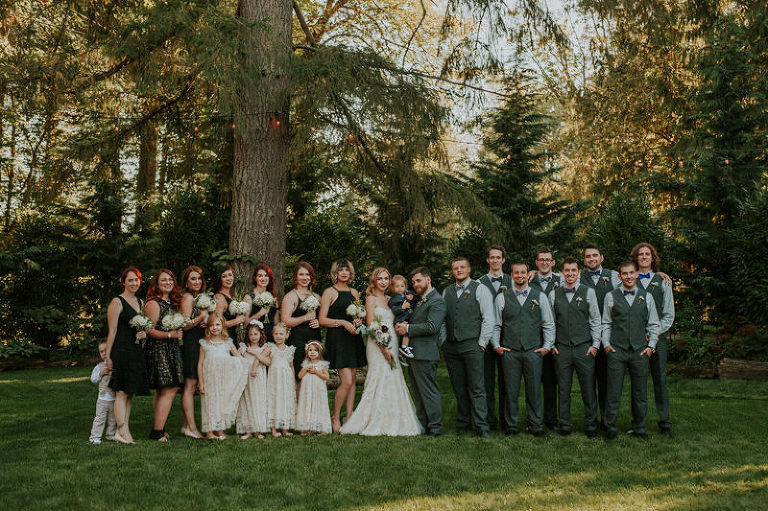 Large Wedding Party With Bridesmaids In Black Dresses And Groomsmen Grey Vests Bow