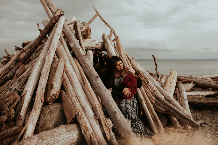 Lifestyle portrait session with a family sitting in a driftwood shelter.