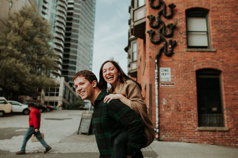 Fun engagement session in downtown Seattle, with groom giving bride a piggy back ride.