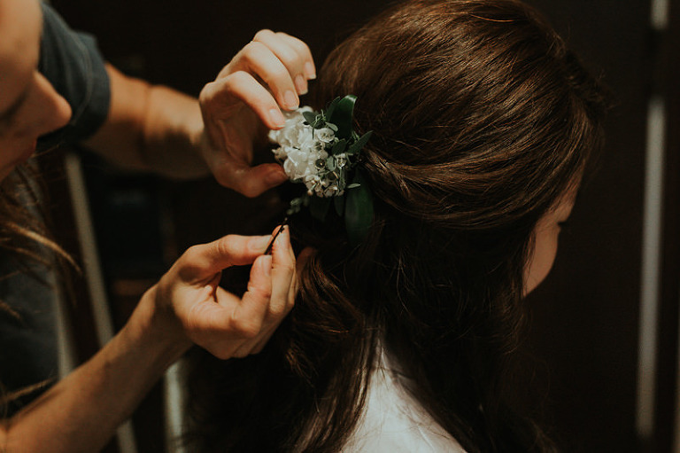 Hairstylist applying fresh floral hairpiece to bride's half updo.