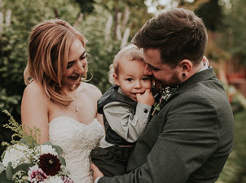 Beautiful bride and groom hold their young son after their wedding in Black Diamond, WA.